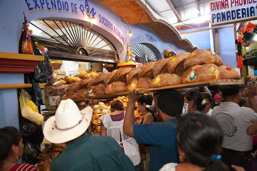 """North America, Mexico, Oaxaca Province, Ocotlan, man delivering special bread (""""'pan de muertos"""")  in crowded market during annual Day of the Dead (Dias de los Muertos) celebration in November"""