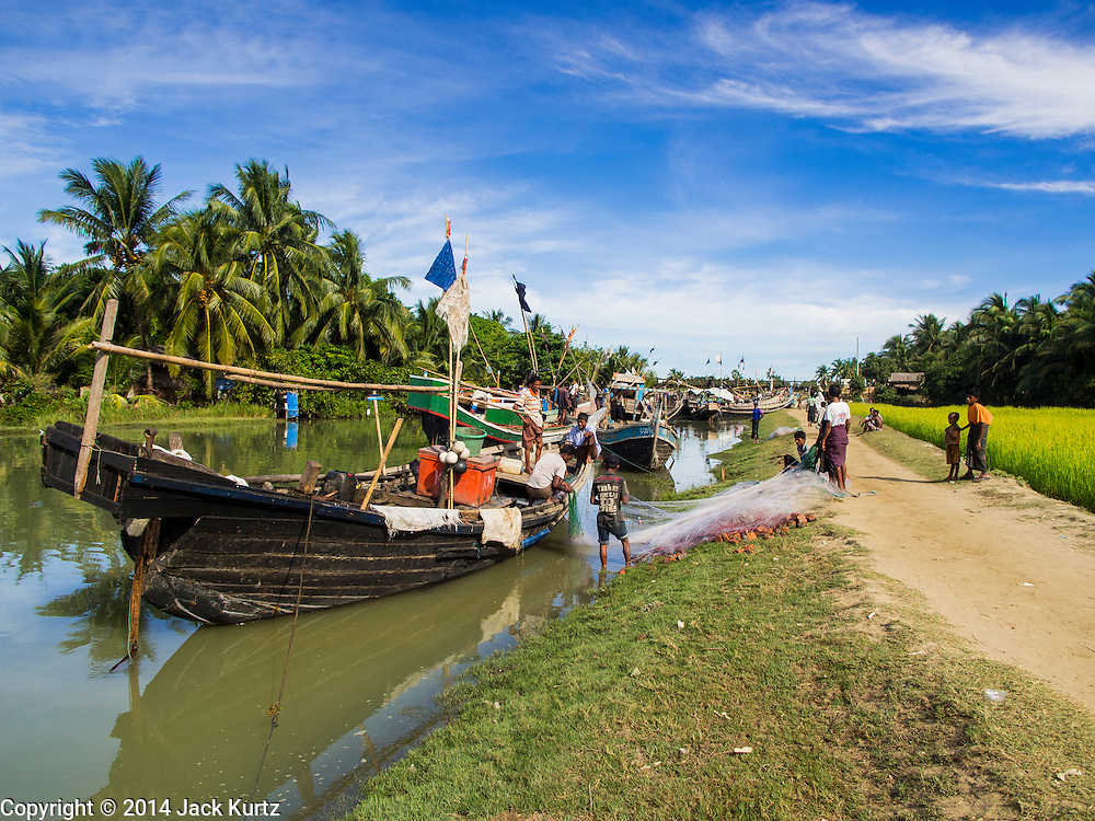 06 NOVEMBER 2014 - SITTWE, RAKHINE, MYANMAR: Fishing boats tied in a creek near an IDP camp for Rohingya Muslims a few miles from Sittwe, Myanmar. The government of Myanmar has forced more than 140,000 Rohingya Muslims who used to live in Sittwe, Myanmar, into squalid Internal Displaced Person (IDP) camps around Sittwe. The forced relocation took place in 2012 after sectarian violence devastated Rohingya communities in Sittwe and left hundreds dead. None of the camps have electricity and some have been denied access to regular rations for nine months. Conditions for the Rohingya in the camps have fueled an exodus of Rohingya refugees to Malaysia and Thailand. Tens of thousands have put to sea in rickety boats hoping to land in Malaysia but sometimes landing in Thailand. The exodus has fueled the boat building boom on the waterfront near the camps. Authorities expect the pace of refugees fleeing Myanmar to accelerate during the cool season, December through February, when there are fewer storms in the Andaman Sea and Bay of Bengal.   PHOTO BY JACK KURTZ