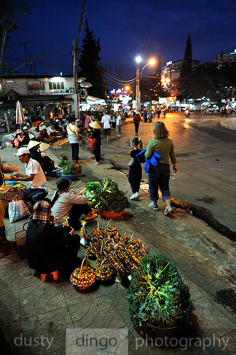 At night, Western woman and her daughter stroll past vendors on the footpath. Broccoli (Bong cai xanh) and dried-flower arrangements for sale on the footpath of central Da Lat, Vietnam