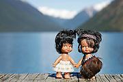 Iconically New Zealand traditional Maori dolls holding hands on jetty at Lake Rotoiti Nelson lakes National Park South Island New Zealand