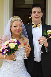 Visually impaired bride and groom celebrating with champagne after marriage ceremony.