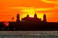Ellis Island silhouetted at sunset, New York harbor, New York, New York USA.