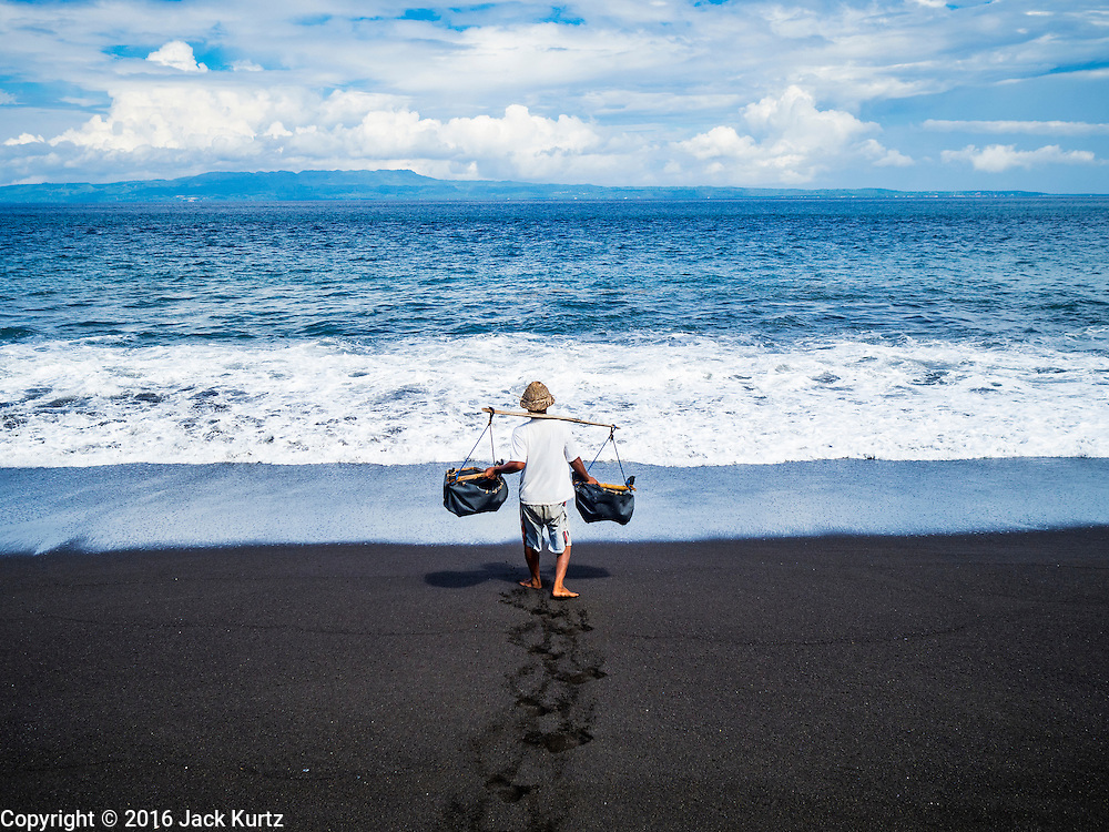 20 JULY 2016  - KUSAMBA, BALI, INDONESIA: A man collects sea water to use to make salt in Kusamba. Salt makers in Kusamba, on the Bali coast, make salt by sprinkling sea water on a bed of sand and scraping up the salt when the water evaporates. It's a very slow, labor intensive way of making salt.       PHOTO BY JACK KURTZ