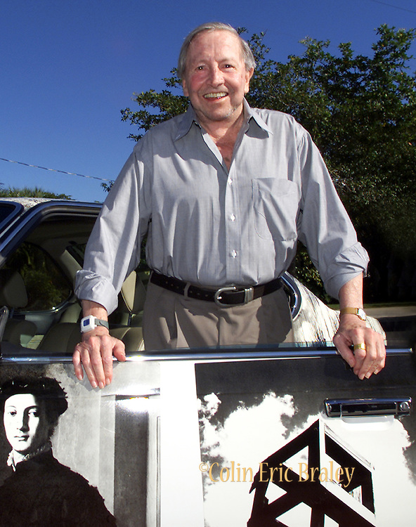 """American pop culture artist Robert Rauschenberg poses next to one of his """"Beamer"""" collages at an art gallery in Naples, Florida in this 2002 file photo. The 82-year-old died Monday, May 12, 2008, of heart failure according to Jennifer Joy, his representative at PaceWildenstein gallery in New York. Rauschenberg's incorporation of everyday items, both common place and the odd in his artwork earned him the reputation as a pioneering pop artist, gaining fame in the 1950's. Photo by Colin Braley."""