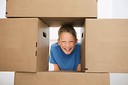 Boy building pile cardboard boxes in new home