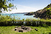 The remnants of a bonfire and logs as seats around it, outside Wolf's Lair with views out across the north coast cliffs and headland in Jersey CI on a sunny Spring day