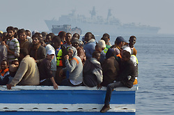 """Migrants stranded on a boat, thirty miles off the Libyan coast as they are rescued by Royal Marines.  PRESS ASSOCIATION Photo. Picture date: Sunday June 7, 2015. The rescued migrants were taken to the Royal Navy ship where they were searched and processed before being handed over to the Italian authorities. Britain is a country that """"doesn't walk on by"""", David Cameron said as HMS Bulwark undertook another rescue mission off Libya. The Royal Navy warship picked up at least 500 migrants found in four boats in the seas off the north African country. Arriving at the G7 summit in Garmisch-Partenkirchen, Germany, the Prime Minister said the flagship had been deployed because the UK is a """"country with a conscience"""".  But he warned that the causes of the mass exodus from Libya must be dealt with, not just the consequences. See PA story DEFENCE Migrants. Photo credit should read: Rowan Griffiths/Daily Mirror/PA Wire"""
