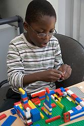 Boy at nursery school playing with Lego