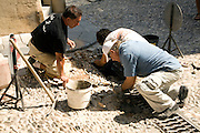 Men repairing cobbled street, Rhodes town, Rhodes, Greece