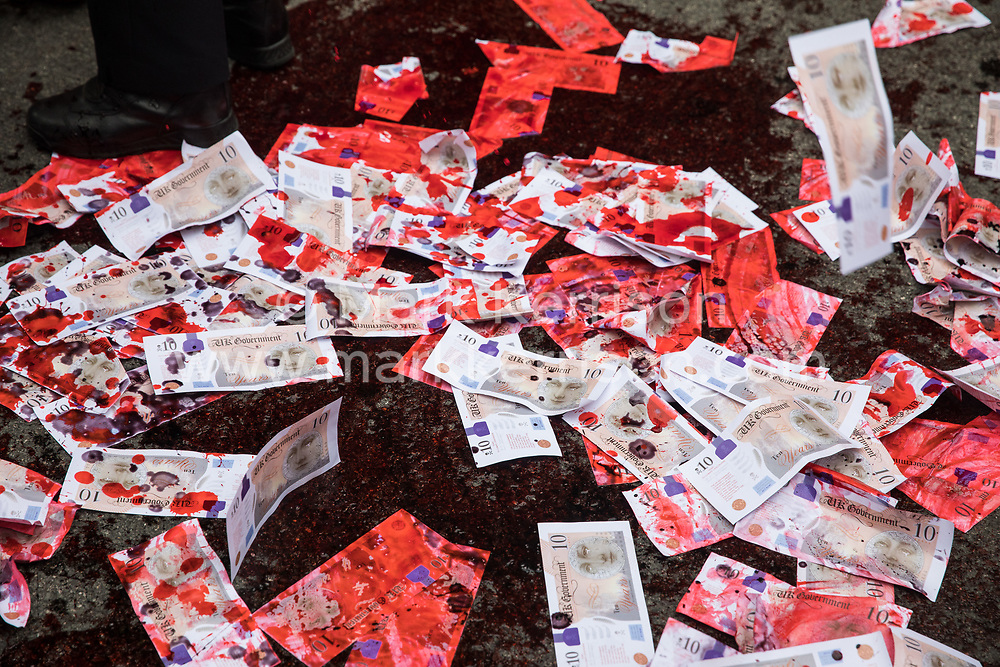 Fake blood and banknotes spread in the road in front of Downing Street during a 'Carnival of Corruption' protest by climate activists from Extinction Rebellion are pictured on 3 September 2020 in London, United Kingdom. Extinction Rebellion activists are attending a series of September Rebellion protests around the UK to call on politicians to back the Climate and Ecological Emergency Bill (CEE Bill) which requires, among other measures, a serious plan to deal with the UK's share of emissions and to halt critical rises in global temperatures and for ordinary people to be involved in future environmental planning by means of a Citizens' Assembly.