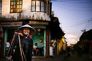 A vietnamese woman with her conical hat smiles at the camera. Hoi An, Vietnam, Asia