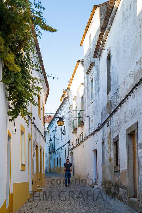 Young man, hands in pockets, in typical street scene of white and yellow houses, lanterns and narrow cobble street, Evora, Portugal