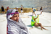 Tourists having fun on the wet floor at Pamukkale. The hard, white mineral deposits, which from a distance resemble snow, are caused by the high mineral content of the natural spring water which runs down the cliff and congregates in warm pools on the terraces. This is such a popular tourist attraction that strict rules had to be established in order to preserve its beauty, which include the fact that visitors may no longer walk on the terraces. Those who want to enjoy the thermal waters, however, can take a dip in the nearby pool, littered with fragments of marble pillars.