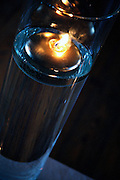 Woodgrain reflecting in glass candle holder.