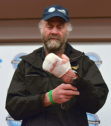 "© Licensed to London News Pictures. 04/03/2013. Heathrow, UK SIR RANULPH FIENNES looks at his bandaged left hand. . Explorer Sir Ranulph Fiennes returns to the UK after pulling out of ""The Coldest Journey"" Expedition to the Antarctic at winter due to frostbite. The Coldest Journey Press Conference today 4th March 2013 at Heathrow Airport. Photo credit : Stephen Simpson/LNP"
