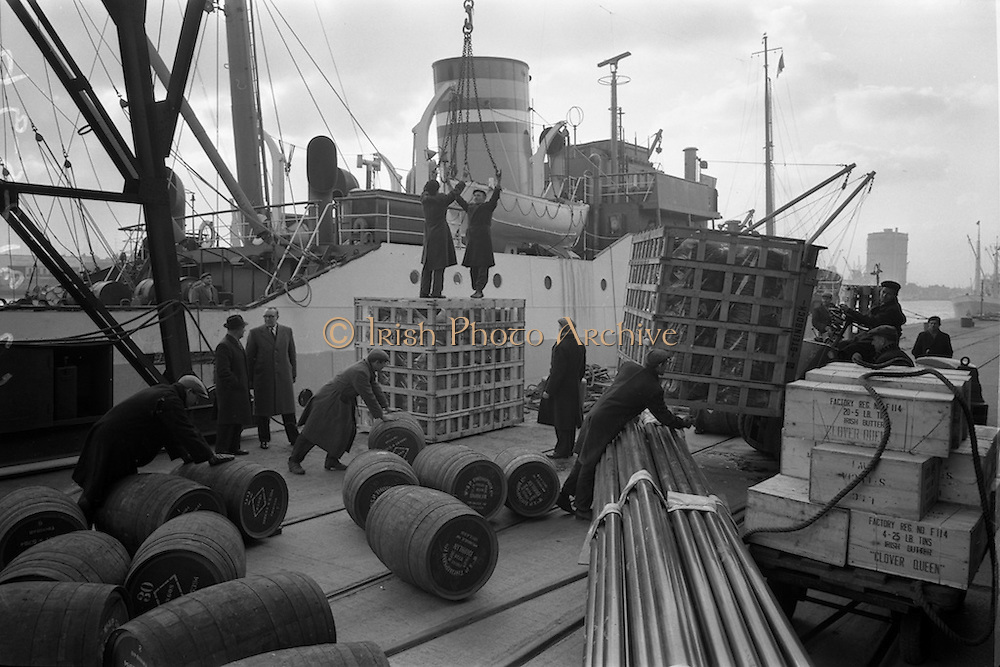 19/02/1963<br /> 02/19/1963<br /> 19 February 1961<br /> Loading M.V. Hardenberg at North Wall, Dublin. Dockers loading a variety of export goods ranging from prune wine to coils of wire at the docks.