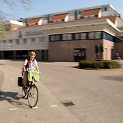 Vrouw fiets met kinderen langs de Rabobank Huizen, haast, druk