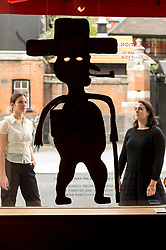 """© Licensed to London News Pictures. 02/10/2018. LONDON, UK. Staff members view a sculpture by Georges Liautaud. Preview of """"Art + Revolution in Haiti"""", an exhibition at The Gallery of Everything in Chiltern Street.  The exhibition, which coincides with Frieze Week, explores when Surrealism arrived in the former slave colony in 1945.  Works from artists from le Centre d'Art d'Haiti and from the personal collection of Andre Breton, the founder of Surrealism, are on display until 11 November 2018.  Photo credit: Stephen Chung/LNP"""