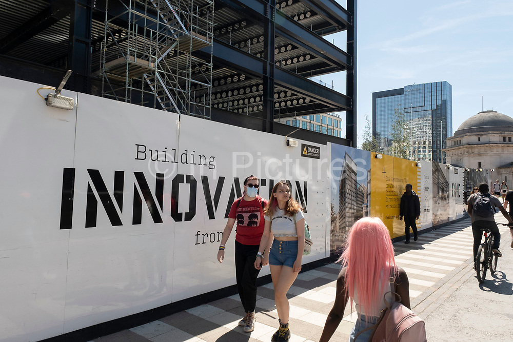 Steel frame of a new building under construction, and building innovation hoarding, as part of the redevelopment of the Paradise area on 15th June 2021 in Birmingham, United Kingdom. Paradise, formerly Paradise Circus, is the name given to an area of approximately 7 hectares in Birmingham city centre between Chamberlain and Centenary Squares. The area has been part of the civic centre of Birmingham since the 19th century. From 2015 Argent Group will redevelop the area into new mixed use buildings and public squares.