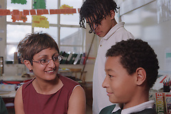 Primary school teacher sitting with pupils in classroom,