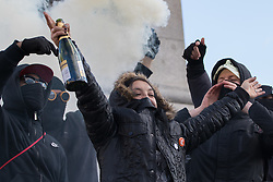 "London, April 16th 2016. A young woman celebrating her birthday and surrounded by black-clad protesters clutches a bottle of Cava as anarchists let off a smoke bomb on the plinth of Nelson's column in Trafalgar Square after thousands of people supported by trade unions and other rights organisations demonstrated against the policies of the Tory government, including austerity and perceived favouring of ""the rich"" over ""the poor""."