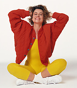 Woman in exercise attire sitting on white seamless paper background relaxing and smiling.