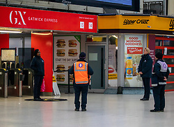 © Licensed to London News Pictures. 28/04/2020. London, UK. Staff at Victoria Station in Westminster stop for the 1 minute silence for fallen key workers. UK holds a minute silence for key workers who have died in the Coronavirus pandemic as the Office for National Statistics reveals there were 1000s of more deaths due to Covid-19 outside of hospitals as the coronavirus pandemic crisis continues. Photo credit: Alex Lentati/LNP