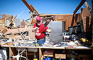 Joe Bell throws debris out of his kitchen in his tornado-destroyed house in Oklahoma City, Oklahoma May 22, 2013.  Rescue workers with sniffer dogs picked through the ruins on Wednesday to ensure no survivors remained buried after a deadly tornado left thousands homeless and trying to salvage what was left of their belongings.  REUTERS/Rick Wilking (UNITED STATES)