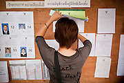 03 JULY 2011 - BANGKOK, THAILAND:   A woman looks for her name on the voter rolls in Bangkok, Thailand, Sunday July 3. More than 47,000,000 Thais were registered to vote in Sunday's election, which had turned into a referendum on the current government, led, by the Thai Democrats and the oppositionPheu Thai party. Pheu Thai is the latest political incarnation of ousted Thai Prime Minister Thaksin Shinawatra. PT is led by his youngest sister, Yingluck Shinawatra, who is the party's candidate for Prime Minister. Exit polling by three Thai polling firms showed Pheu Thai winning a landslide election.   PHOTO BY JACK KURTZ