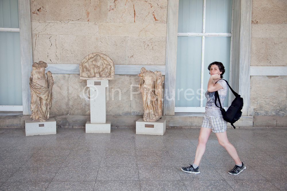 Tourist at The Stoa of Attalos or Attalus located in the east side of archaeological site of the Ancient Agora in Athens just oposite the Adrianou street in Monastiraki. The Stoa of Attalos was built around 150 BC, by Attalos II, King of Pergamos as a donation to Athens. The construction of the building began in 159 BC and ended in 138 BC. The building was the largest in length in Greece during the antiquity. It was rebuilt in the same style and shape from 1953 to 1956 with beautifully crafted marble columns. It is recognised as one of the most impressive stoa in the Athenian Agora. Typical of the Hellenistic age, the stoa was more elaborate and larger than the earlier buildings of ancient Athens. The stoa's dimensions are 115 by 20 metres wide (377 by 65 feet wide) and it is made of Pentelic marble and limestone. The building skillfully makes use of different architectural orders. The Doric order was used for the exterior colonnade on the ground floor with Ionic for the interior colonnade. Athens is the capital and largest city of Greece. It dominates the Attica periphery and is one of the world's oldest cities, as its recorded history spans around 3,400 years. Classical Athens was a powerful city-state. A centre for the arts, learning and philosophy.