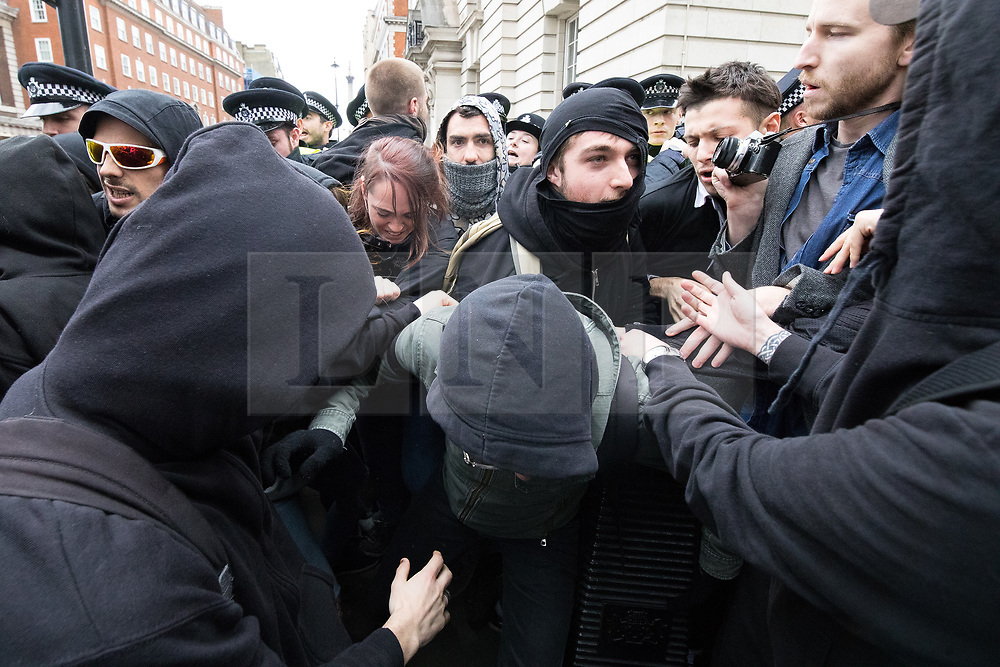© Licensed to London News Pictures . 01/04/2017 . London , UK . Police clash with anti fascist protesters on Whitehall . The EDL and Britain First both hold demonstrations in London , opposed by anti-fascist groups , including Unite Against Fascism . Photo credit : Joel Goodman/LNP