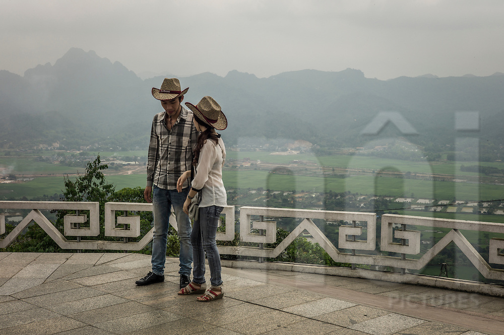 Young Vietnamese couple wearing cowboy hats stands on Tuong Hill overlooking the Hoa Binh dam, Hoa Binh, Vietnam, Southeast Asia