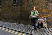 Lucinda Rogers, a contemporary British artist sketches on a street in London, United Kingdom. Rogers is widely known as an illustrator of newspaper columns.