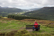 A walker rests on a bench while on the Precipice Walk, to overlook the landscape of the river Afon Mawddach and out to the sea at Barmouth, on 13th September 2018, in Dolgellau, Gwynedd, Wales.