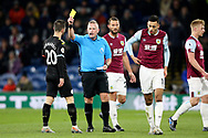 Referee Jonathan Moss  shows the yellow card to Manchester City midfielder Bernardo Silva (20) for the foul on Burnley midfielder Dwight McNeil (11) during the Premier League match between Burnley and Manchester City at Turf Moor, Burnley, England on 3 December 2019.