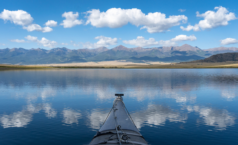 Bow shot of kayak shows clouds and Sangres reflected in Lake DeWeese.