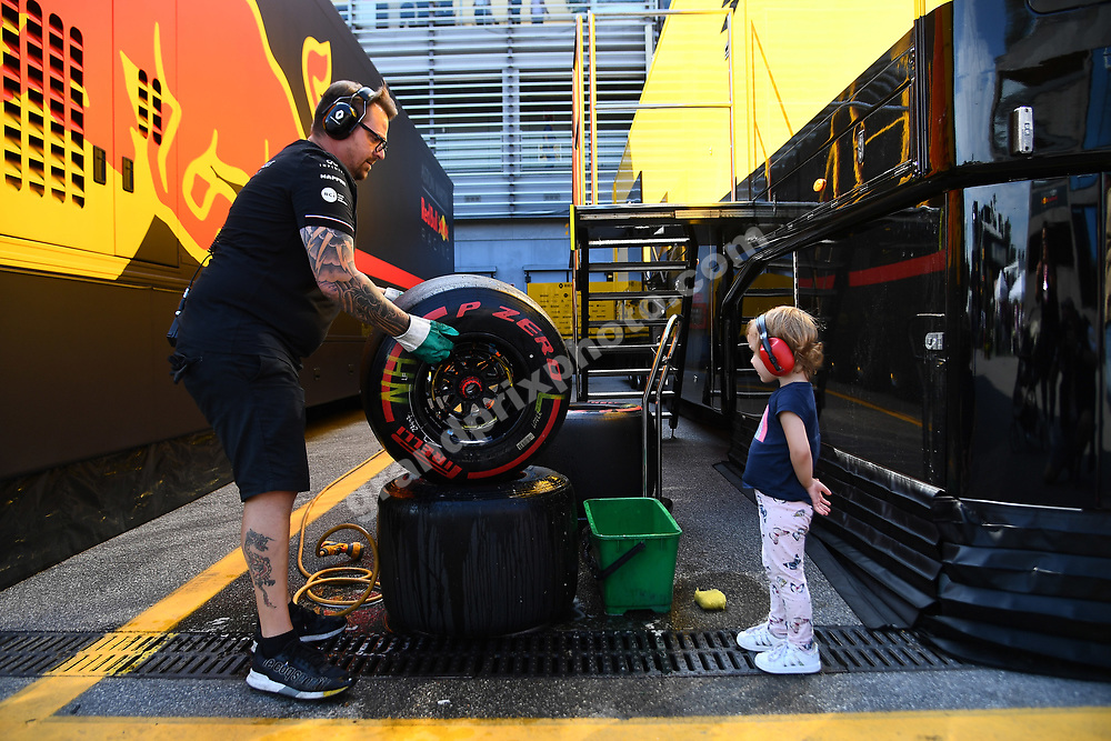 Renault mechanic with tyre and child after qualifying for the 2019 Italian Grand Prix in Monza. Photo: Grand Prix Photo