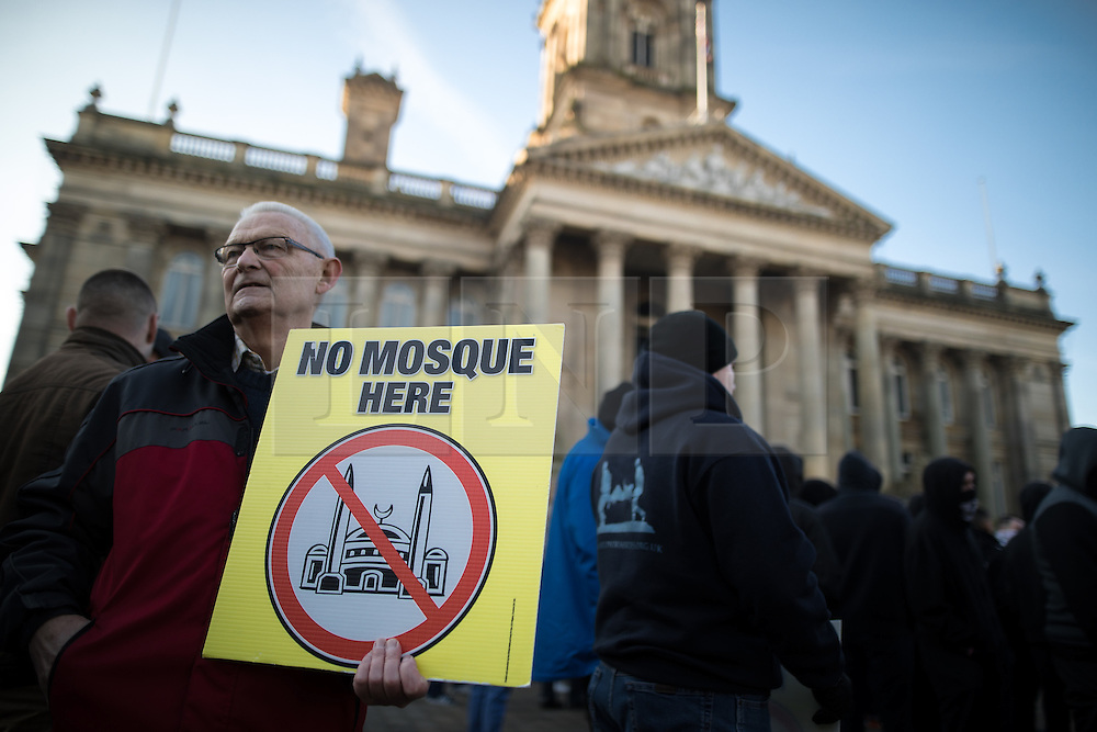 """© Licensed to London News Pictures . 26/11/2016 . Bolton , UK . Those opposed to mosques pictured at the demonstration . Approximately 100 people attend a demonstration against the construction of mosques in Bolton , under the banner """" No More Mosques """" , organised by a coalition of far-right organisations and approximately 150 anti fascists opposing the demonstration , in Victoria Square in Bolton Town Centre . Photo credit : Joel Goodman/LNP"""