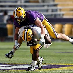 April 9, 2011; Baton Rouge, LA, USA;  LSU Tigers linebacker D.J. Welter (purple) tackles running back Spencer Ware (white) during the 2011 Spring Game at Tiger Stadium.   Mandatory Credit: Derick E. Hingle