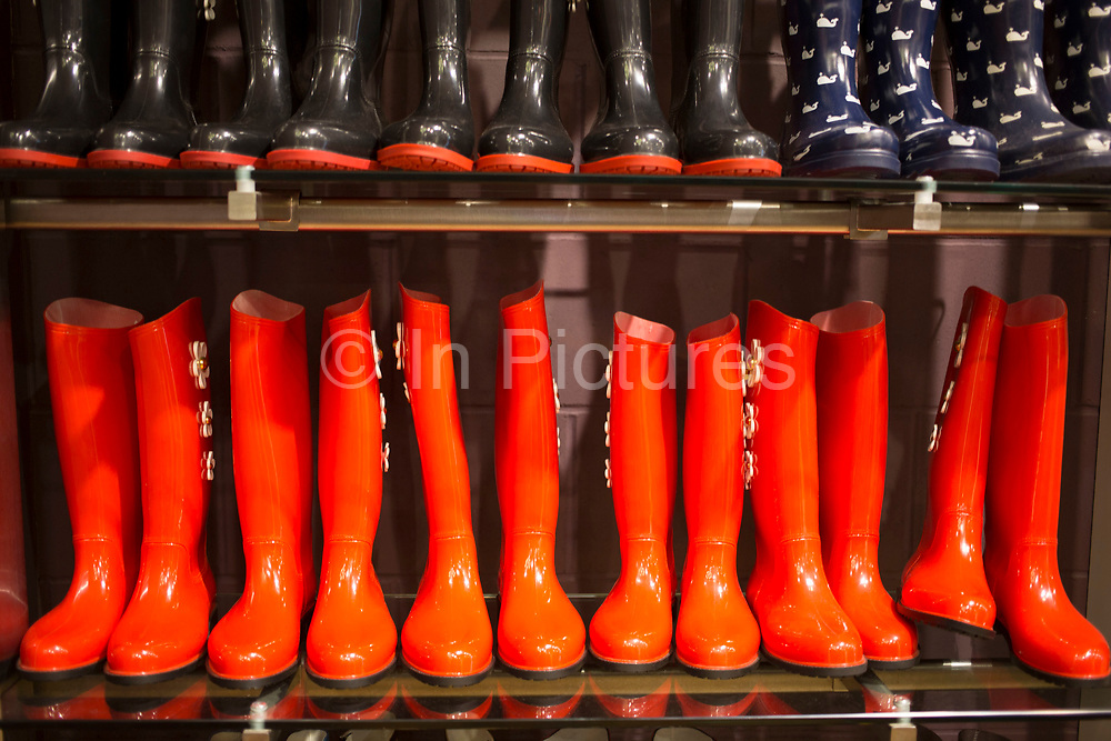 Orange and black wellies on sale during a wet season at a clothes retailer. Wellington or rubber boots sales have increased dramatically during the wet winter season in the UK, and it is common to see people walking around in the street with them on.