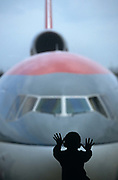 A boy spreads his hands and fingers out on a Gatwick South Terminal window. Outside is the nose of an American Northwest Airlines DC-10 with its third engine mounted high on the rear fuselage) that is parked at a satellite gate at London Gatwick airport. The boy is a silhouette against subdued light and the aircraft's nose resembles a shark's face that is menacingly close to the young child. Such is the flattening of perspective by a telephoto lens, the aircraft looks much closer than in reality. Gatwick airport, as well as Heathrow, Stansted, Aberdeen, Edinburgh, Glasgow and Southampton in the UK, is owned and administered by BAA, the British Airport Authority.