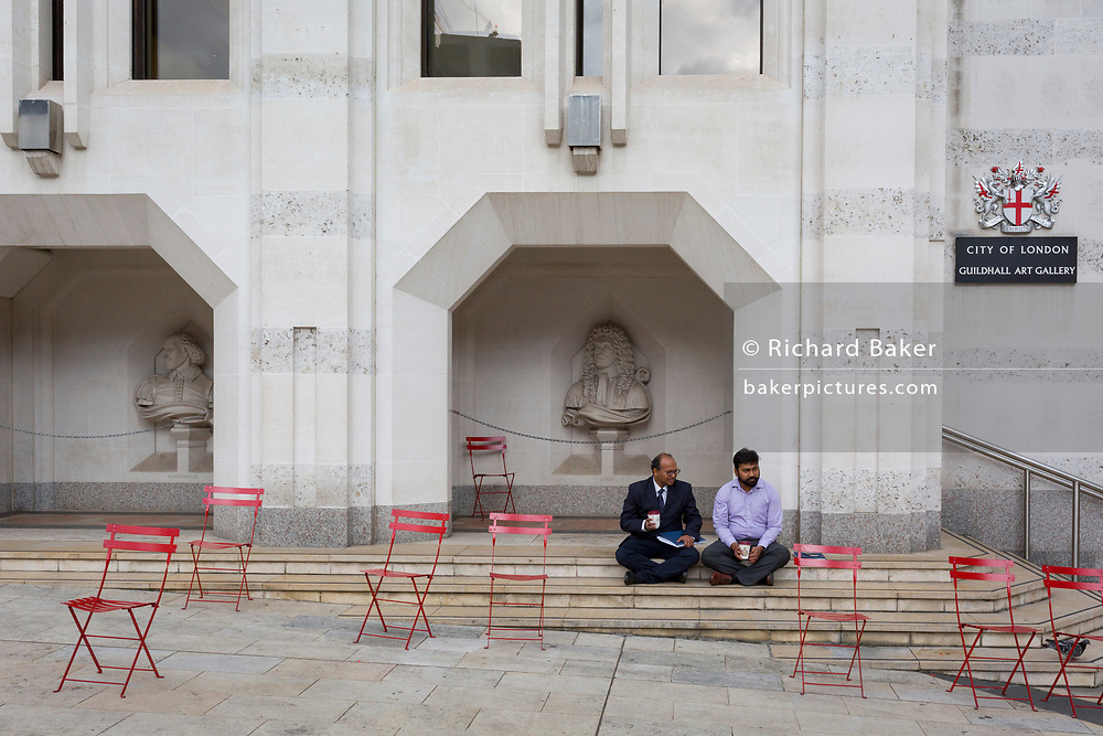 Two men prefer to sit on the steps of the Guildhall Art Gallery, rather than on available chairs, on 14th September 2017, in the City of London, England.
