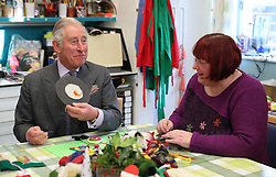 The Prince of Wales helps make Christmas decorations during a visit to the Sue Ryder Leckhampton Court Hospice near to Cheltenham in Gloucestershire, which he visits regularly and is celebrating 30 years of royal patronage.