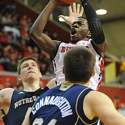 Rutgers Scarlet Knights guard Eli Carter (5) shoots a basket over Notre Dame Fighting Irish forward Jack Cooley (45) and guard/forward Pat Connaughton (24) during Big East NCAA action during Rutgers' 65-58 victory over Notre Dame at the Louis Brown Athletic Center in Piscataway, N.J.
