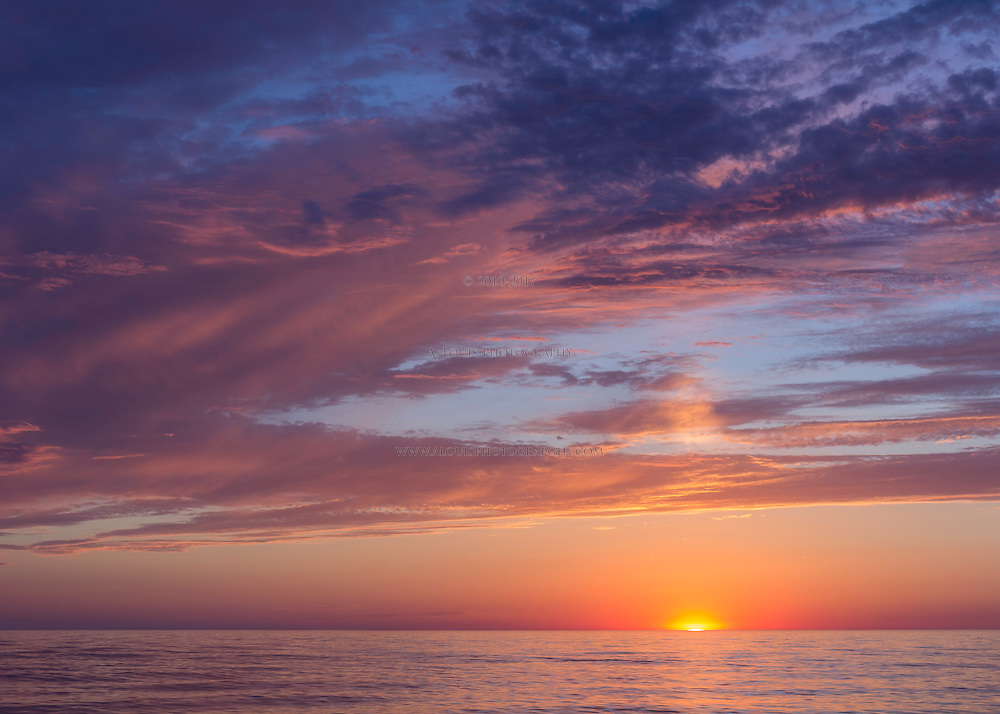 The sun colors the sky before setting on Lake Michigan
