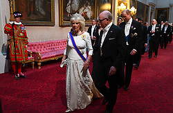 Duchess of Cornwall and Robert Wood Johnson, the United States Ambassador to the United Kingdom, arrive through the East Gallery during the State Banquet at Buckingham Palace, London, on day one of the US President's three day state visit to the UK.