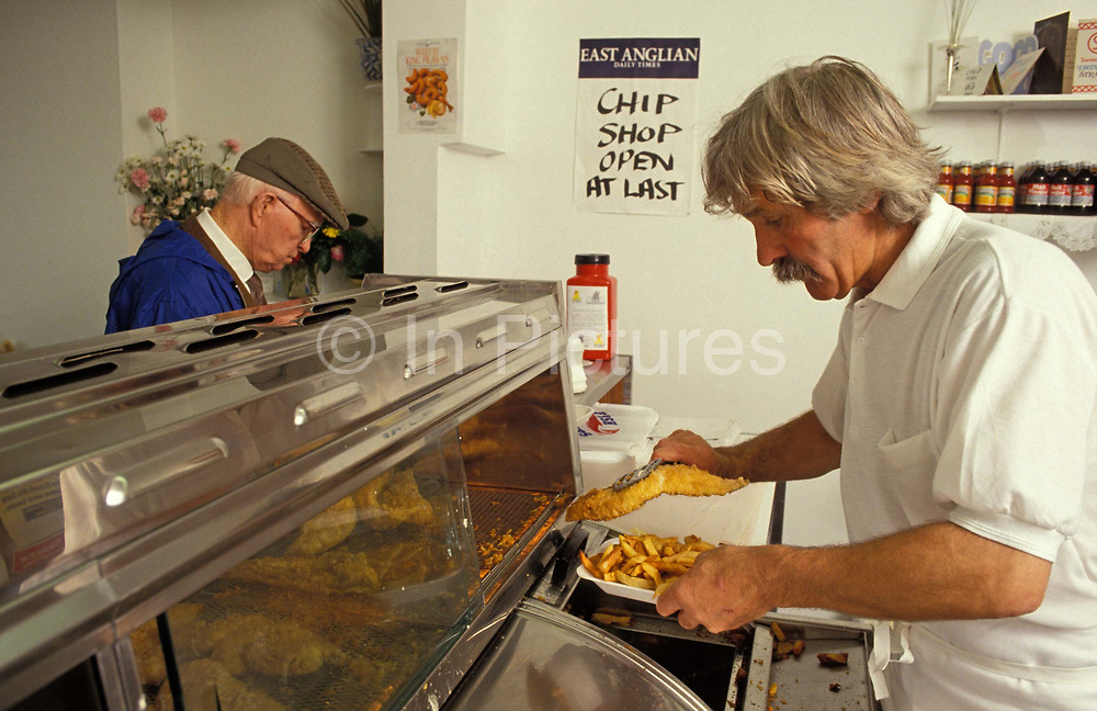 A chip shop owner serves up some battered fish and chips to a customer in Nice Fish and Chips on Old Road, the first fish and chip business in the conservative Essex seaside town of Frinton-on-Sea, on 26th June 1992, in Frinton, England.