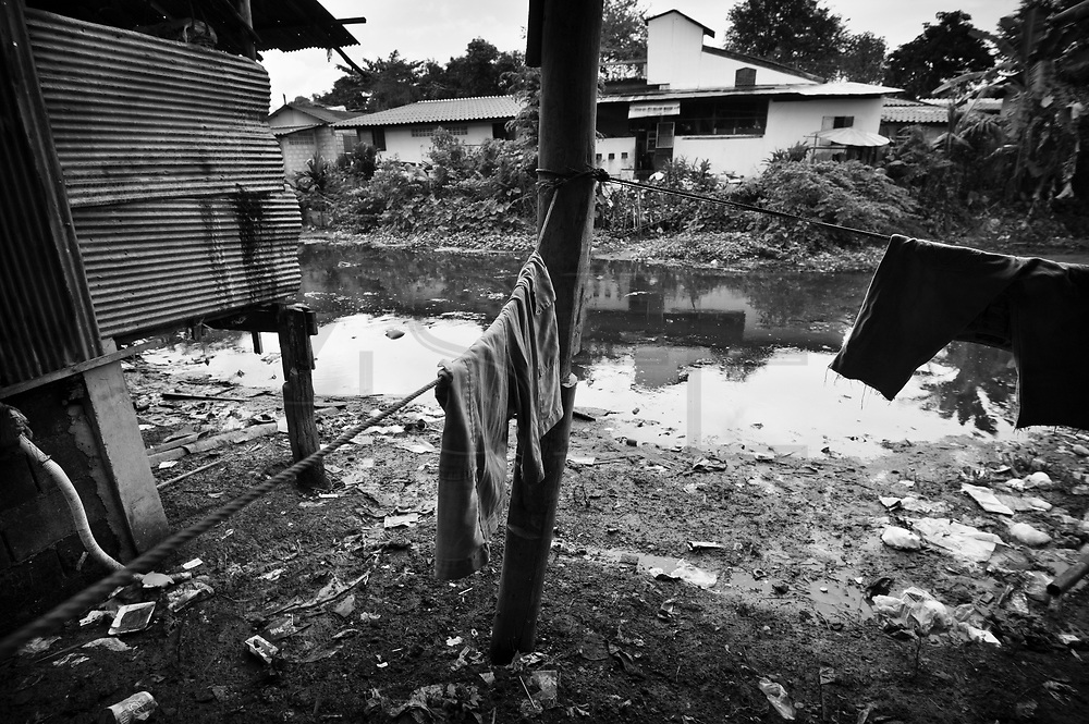Clothes hanging out to dry by the polluted river. During heavy rain the water rises above this level and almost all the way into the houses.On the banks of a polluted river, in poorly-built houses, live more than a hundred people from the Lahu tribe. They live in a slum in Chiang Mai, Thailand, away from the Lahu people's original way of life. Usually, the Lahu people get their resources from the forest. The slum has been there for decades.