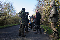 Denham, UK. 11 February, 2020. Environmental activists from Extinction Rebellion, Stop HS2 and Save the Colne Valley are interviewed by Andy Bell of Channel 5 News as they 'slow walk' in front of a large truck transporting a JCB forklift truck to a HS2 site at Denham in the Colne Valley. Contractors working on behalf of HS2 are rerouting electricity pylons through a Site of Metropolitan Importance for Nature Conservation (SMI) in conjunction with the high-speed rail link.