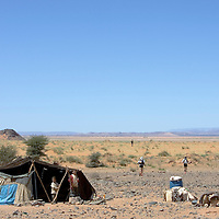 27 March 2007: Participants run by a nomad's tent en route to the bivouac during third stage of the 22nd Marathon des Sables between jebel El Oftal and jebel Zireg (20.07 miles). The Marathon des Sables is a 6 days and 151 miles endurance race with food self sufficiency across the Sahara Desert in Morocco. Each participant must carry his, or her, own backpack containing food, sleeping gear and other material.